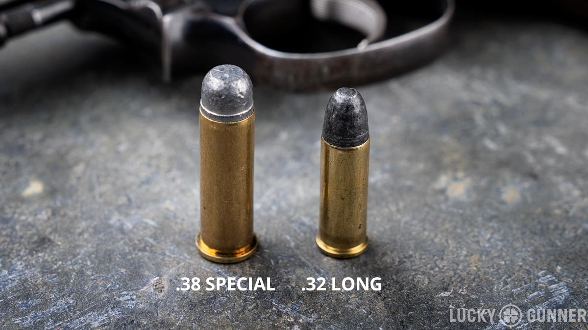 38 special ammo next to 32 long ammo on a table with a revolver